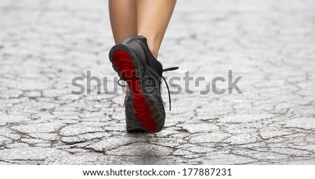 back shot of young lady with fitness old shoes in act to walking ,running on a broken fashion road .  - stock photo