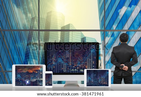 Back side of Businessman looking at city out off windows glass with Computer set show Trading graph on the cityscape and world map background on the table in meeting room,Business financial concept - stock photo