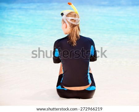 Back side of calm diver girl sitting on seashore, wearing snorkeling equipment and resting on the beach, summer adventure and traveling concept - stock photo