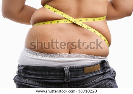 Back side of fat woman with measuring tape, a concept to get a diet - stock photo