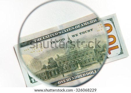 "Back side of 100 US Dollar under magnifying glass aiming ""In God we trust"" Sign"