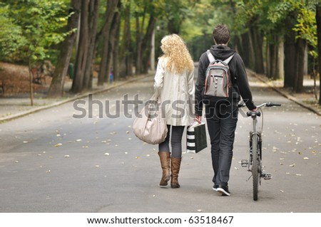 back side view of two teenagers walking in park and a bile