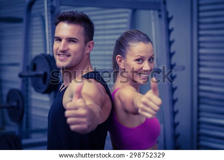 Back to back muscular couple gesturing thumbs up - stock photo