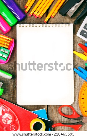 Back to school. A notebook and school tools around. Vertically. A wooden background. - stock photo