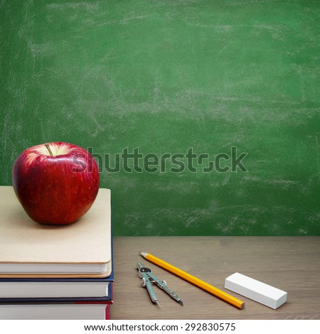Back To School - A Red Apple on a Pile of Books in front of a Chalkboard - stock photo