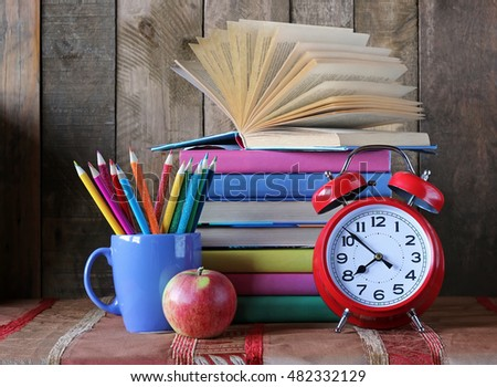 Back to school. A stack of books, crayons, Apple and clock on the table. Still life with books. School books in colorful covers.
