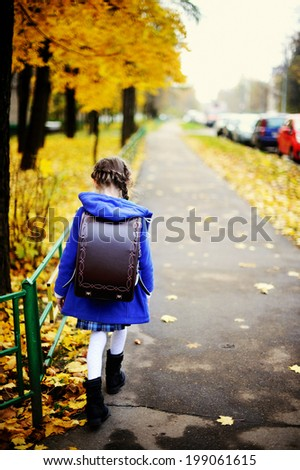 Back to school - adorable brunette girl in blue coat and brown stylish school bag on her way to the school by the autumn city street with yellow trees