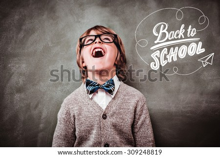 back to school against boy laughing in front of blackboard - stock photo