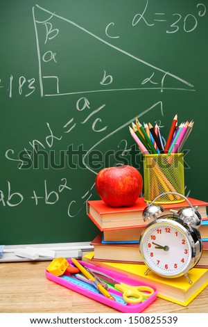 Back to school. An alarm clock, books and school accessories against a school board (mathematical formulas).