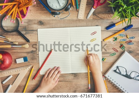 Back To School And Happy Time! Wooden Desk With Supplies. A Child Writes  In. View Preview