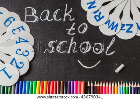 "Back to school background with a lot of colorful felt-tip pens and colorful pencils,  cards of numerals from one to ten and title ""Back to school"" written by white chalk on the black school chalkboard - stock photo"