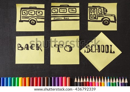 "Back to school background with a lot of colorful felt-tip pens and colorful pencils, titles ""Back to school"" and drawing of school bus drawn on the yellow pieces of paper on the  school chalkboard - stock photo"