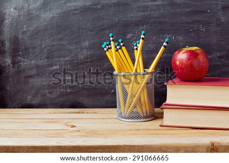 Back to school background with books, pencils and apple over chalkboard - stock photo