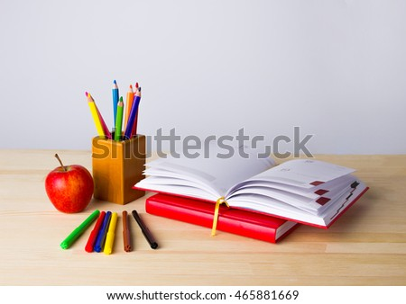 Back to school background with books, pencils and apple over wooden table