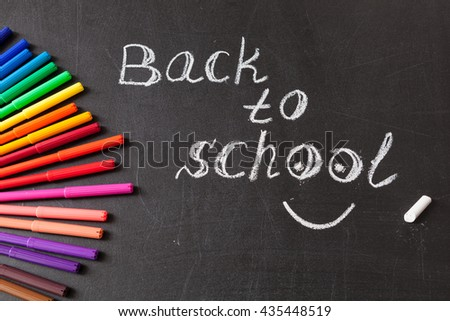"Back to school background with colorful felt tip pens and title ""Back to school"" written by white chalk on the chalkboard - stock photo"