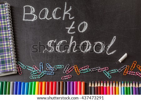"Back to school background with colorful felt tip pens, pencils, clips, notebook and the title ""Back to school"" written by white chalk on the black school chalkboard"