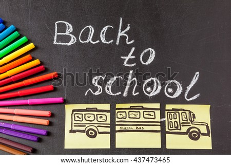 "Back to school background with colorful felt tip pens, pencils,  title ""Back to school"" written by white chalk and image of the school bus drawn on yellow pieces of paper on the chalkboard - stock photo"