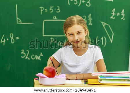 Back to school - beautiful schoolgirl in the classroom - stock photo