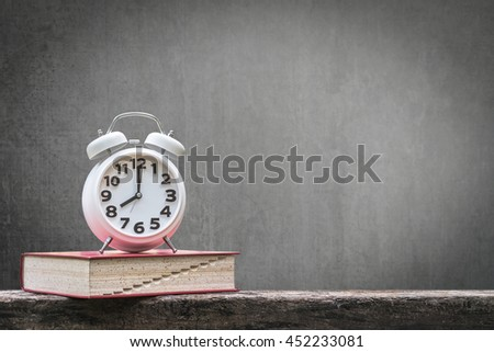 Back to school: Black chalkboard background for announcement w/ wake up alarm clock & textbook on grunge old dark wood table top+ copyspace: Students' educational time for learning system concept - stock photo
