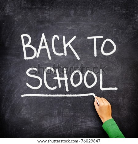 Back to school blackboard / chalkboard. Teacher writing back to school on black chalk board. - stock photo