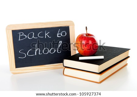back to school: blackboard slate and stack of books with apple on top over white background
