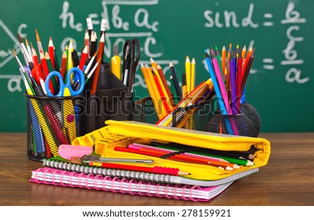 Back to school - blackboard with pencil-box and school equipment on table - stock photo