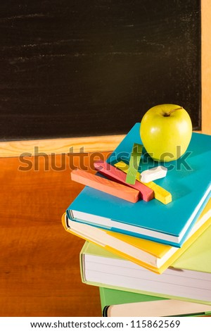 Back to school books and apple, colorful chalks and board