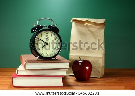 Back to School Books, Lunch, Apple and Clock on Desk - stock photo