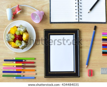 Back to school. Colorful Office and study art stationery objects on wood table with open notebook and Blank photo frames.Kid love to drowing. - stock photo