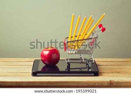 Back to school concept. Apple and pencils with tablet device on wooden table - stock photo