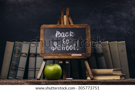 Back to school concept. Background with vintage blackboard, alarm clock, old books, green apple - stock photo