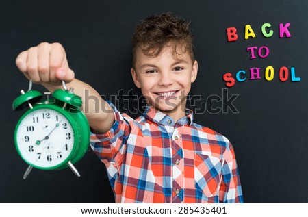 Back to school concept. Boy with big green alarm clock on black chalkboard background.  - stock photo