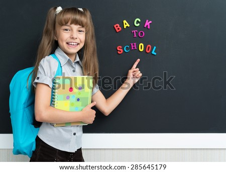 Back to school concept. Cheerful schoolgirl with backpack at the black chalkboard in classroom.