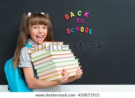 Back to school concept. Cute pupil with books at the black chalkboard in classroom. - stock photo
