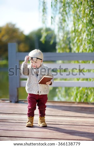 Back to school concept. Funny serious nerd with book outdoors - stock photo