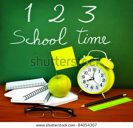 Back to school concept, green chalkboard with handwriting and set of colorful student accessories - stock photo