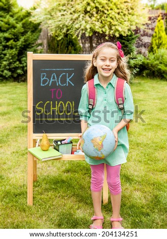 Back to school concept. Happy smiling six years old blond caucasian child girl standing outdoor in front of the chalkboard - education. - stock photo