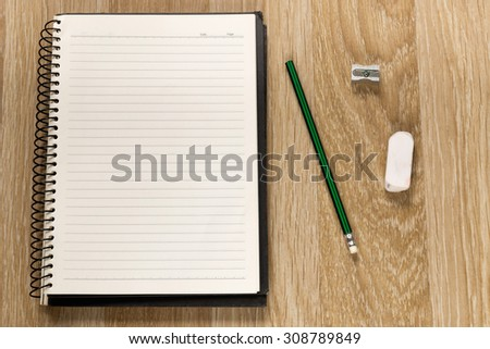 Back to School concept pencil, pencil sharpener, eraser and pad on wooden school desk from above. - stock photo