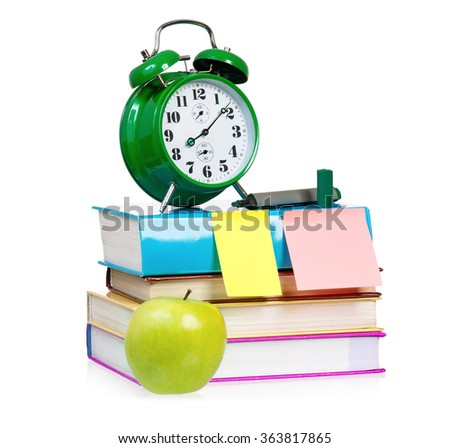 Back to school concept - school accessories. Big green alarm clock with books and apple - isolated on white background.