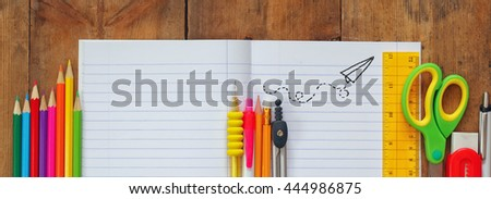 Back to school concept. School supplies on wooden desk with empty open notebook for copy space. website wide format - stock photo
