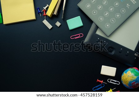 Back to school concept. School supplies with calculator and ebook on blackboard background. Back to school concept with stationery. Schoolchild and student studies accessories. Top view. - stock photo