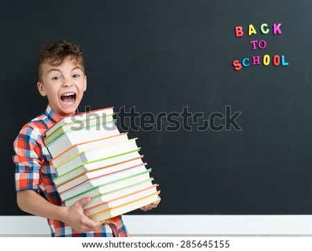 Back to school concept. Schoolboy with books at the black chalkboard in classroom. - stock photo