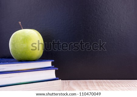 Back to school concept with a blackboard some books and apple