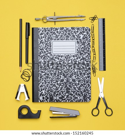 Back to School concept, with a closed theme book surrounded by school supplies. - stock photo