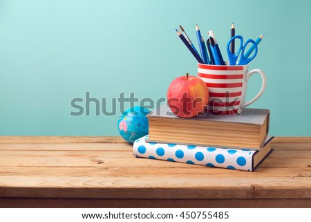 Back to school concept with books, pencils in cup, apple, and globe on wooden table - stock photo