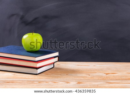 Back to school concept with green apple and books on desk in front of erased black chalkboard.