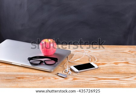 Back to school concept with modern technology consisting of laptop, cell phone, thumb drive and reading glasses in front of erased black chalkboard.