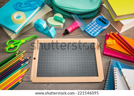 Back to school concept with small chalkboard and multicolor stationery on wooden surface. - stock photo