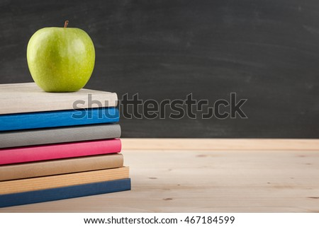 Back to school concept with stack of notebooks and green apple on blackboard background