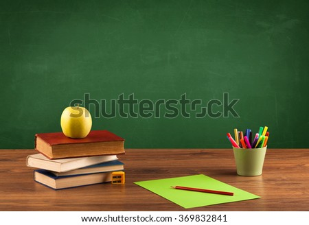 Back to school concepty with clear blackboard background, desk, items - stock photo